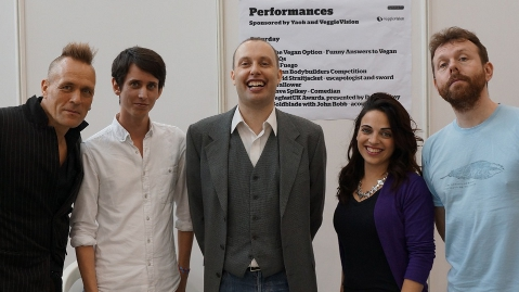 Five people in front of the performance stage timetable
